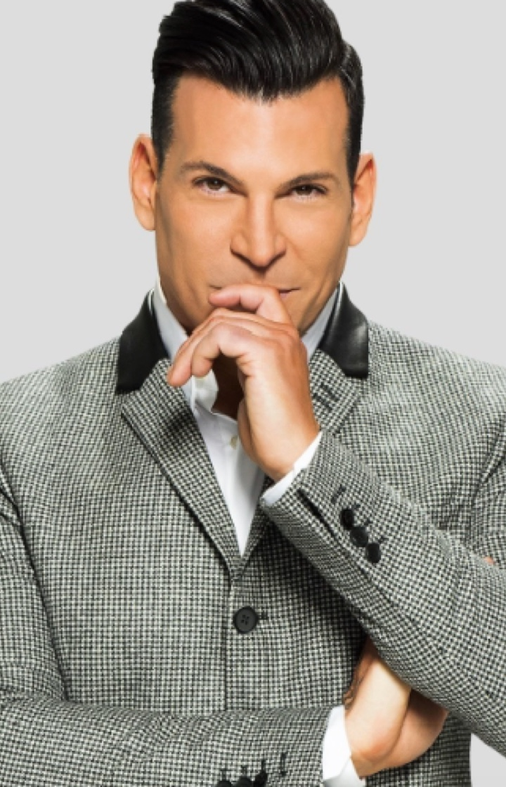 David Tutera stands in grey suit with his hand on his chin in thought.