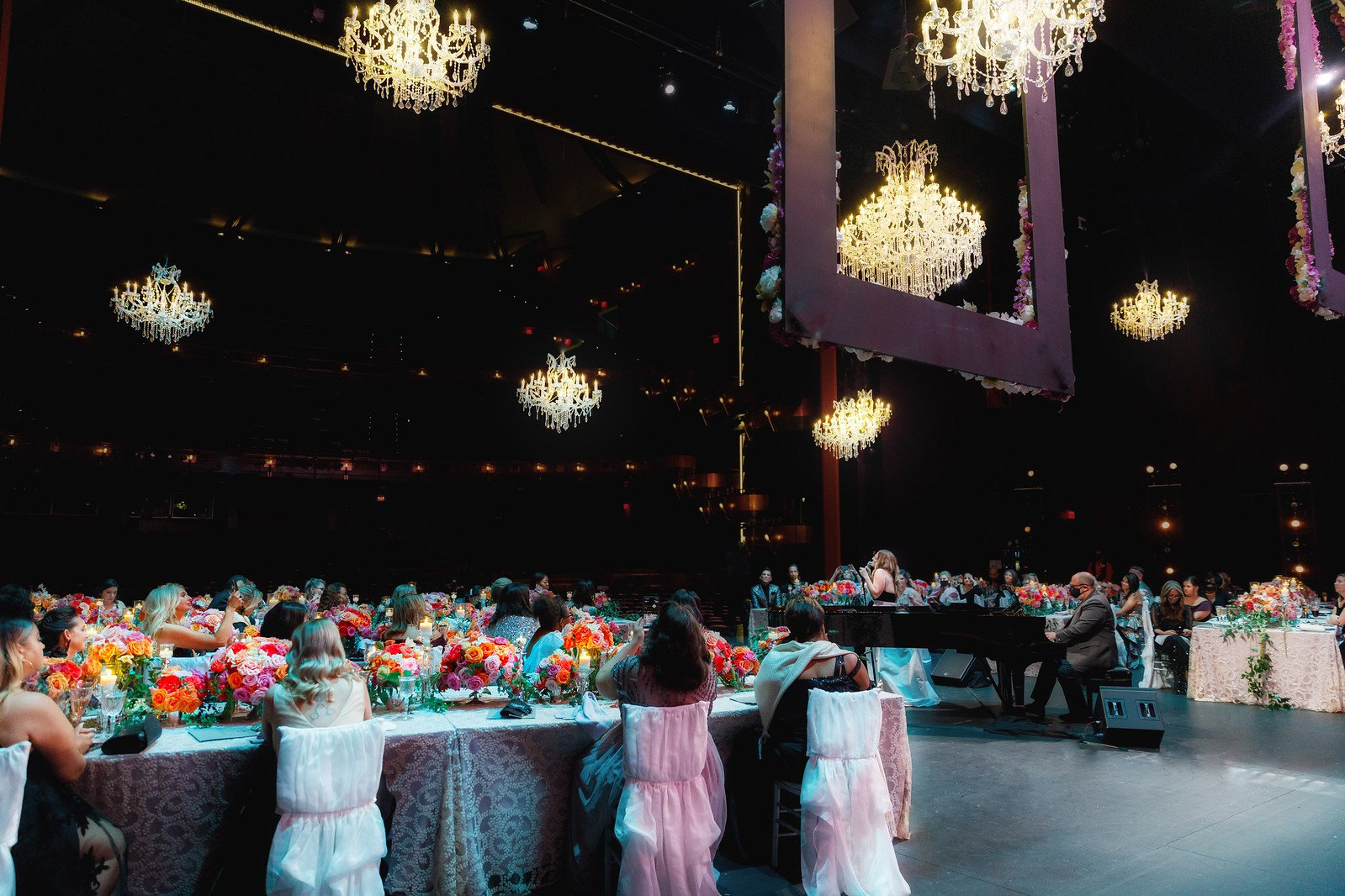 A large group of people sitting at formal dining tables listen to a singer and pianist performing in the center of them all.